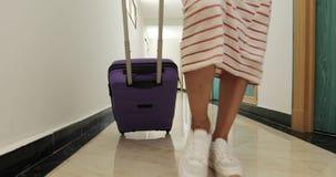 Primer de una mujer que camina a través del pasillo del hotel con una maleta en las ruedas metrajes