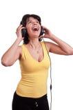 Primer de una mujer que escucha la música en los auriculares que disfrutan de una danza en el fondo blanco Fotos de archivo libres de regalías