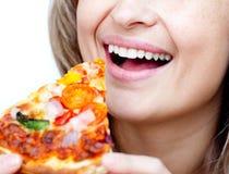 Primer de una mujer sonriente que come una pizza Foto de archivo
