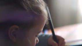 Primer de una niña linda 3-4 años que dibujan en su libro de colorear que se sienta en la tabla almacen de metraje de vídeo