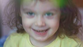 Primer de una niña pequeña hermosa 3-4 años con los ojos azules hermosos que sonríen feliz en la cámara metrajes