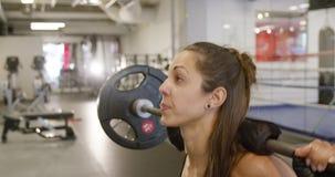 Primer de una posición en cuclillas deportiva del entrenamiento de la mujer con los pesos pesados en gimnasio de la aptitud metrajes