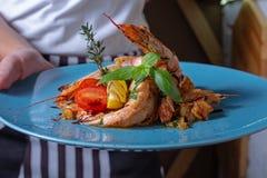 Primer de una situación del camarero en un bistro de moda que sostiene un plato del camarón imágenes de archivo libres de regalías