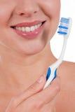 Primer de una sonrisa de la mujer del yougn con el cepillo de dientes Imagen de archivo libre de regalías