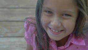 Primer de una sonrisa hermosa de la niña linda en la cámara almacen de video