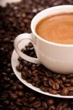 Primer de una taza de café y de habas calientes Fotos de archivo libres de regalías
