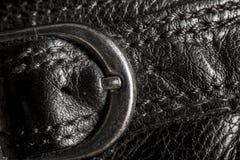 Primer de una textura de cuero con las piezas de metal Fotografía de archivo