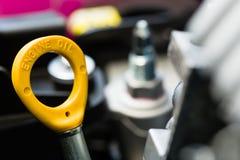 Primer de una varilla graduada amarilla del aceite de motor Imagen de archivo