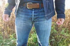 Primer de vaqueros y de una chaqueta del dril de algodón del hombre que llevan Fotografía de archivo