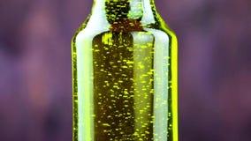 Primer de verter el aceite de oliva en la botella en el fondo de madera