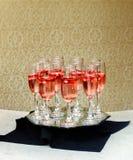 Primer de vidrios de champán en fila en un champán de la porción del champán de la tabla en una bandeja Fotografía de archivo
