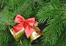 Primer del árbol de navidad con las campanas del oro y el arco rojo Imagen de archivo libre de regalías