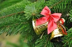 Primer del árbol de navidad con las campanas del oro y el arco rojo Imagen de archivo