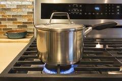 Primer del acero inoxidable que cocina el pote en estufa de gas en cocina casera exclusiva contemporánea Fotos de archivo