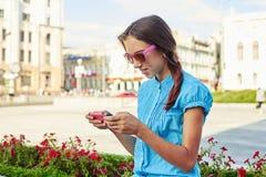 Primer del adolescente bonito en gafas de sol rosadas usando su smartph Fotos de archivo libres de regalías