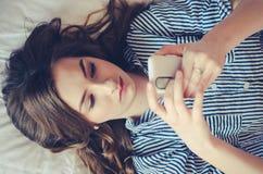 Primer del adolescente bonito que miente en cama una mirada de su teléfono móvil Fotos de archivo