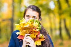Primer del adolescente sonriente joven que sostiene el ramo de las hojas de otoño Temporada de otoño Fotografía de archivo libre de regalías