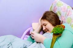 Primer del adolescente triste que miente en cama usando su móvil Muchacha bonita joven con la expresión agujereada que mira el me Foto de archivo