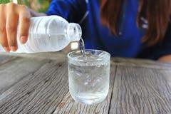 Primer del agua de colada de la mujer joven de una botella plástica en el vidrio en la tabla en restaurante imagen de archivo