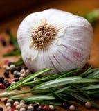 Primer del ajo, del romero fresco y de los granos de pimienta imagenes de archivo