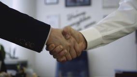 Primer del apretón de manos en el fondo de la oficina El buen negocio aseguró sociedad con el apretón de manos Dos compañeros de  almacen de video