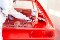 Primer del arma de la pintura de espray con el trabajador que trabaja en un coche rojo Fotos de archivo libres de regalías