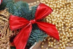 Primer del arreglo rojo de la Navidad del arco con el fondo ligero abstracto defocused de las gotas de oro Imagen de archivo