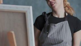 Primer del artista de sexo femenino en el delantal con la paleta Ella hace manchas con una espátula en imagen El concepto de uno