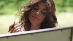 Primer del artista moreno soñador hermoso de la mujer con el lápiz en las manos que pintan la imagen al aire libre en el bosque almacen de video
