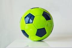 Primer, del balón de fútbol verde en un fondo blanco Concep de la afición Fotografía de archivo