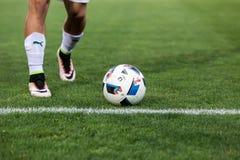 Primer del balón de fútbol y pies del jugador Fotografía de archivo libre de regalías