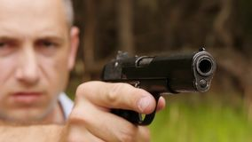 Primer del barril de arma El hombre mira la vista del arma, haciendo un tiro Un hombre tira un arma almacen de metraje de vídeo