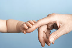 Primer del bebé que sostiene el finger del hombre Imagen de archivo