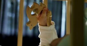 Primer del beb? curioso adorable que juega con el juguete de madera en la cama Poco beb? que juega con los juguetes de madera en  almacen de metraje de vídeo