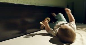 Primer del beb? curioso adorable que juega con el juguete de madera en la cama Poco beb? que juega con los juguetes de madera en  almacen de video