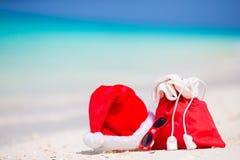 Primer del bolso rojo de Papá Noel y sombrero de Santa Claus en la playa Vacaciones del viaje de Navidad y concepto del cuprise d Fotografía de archivo libre de regalías