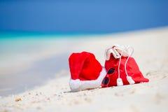 Primer del bolso rojo de Papá Noel y sombrero de Santa Claus en la playa Vacaciones del viaje de Navidad y concepto del cuprise d Foto de archivo libre de regalías