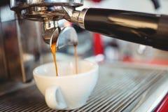 Primer del café de colada del fabricante de café express en el café Foto de archivo libre de regalías