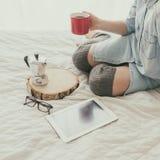 Primer del café de consumición de la mujer joven mientras que se sienta en cama Foto de archivo