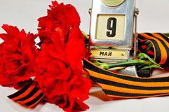 Primer del calendario de escritorio del metal del vintage con la fecha del 9 de mayo y cinta de George y claveles rojos Fotos de archivo