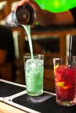 Primer del camarero experto que hace el azul, la turquesa y los cócteles rojos en barra Fotografía de archivo libre de regalías