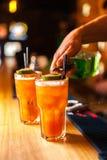 Primer del camarero experto que hace los cócteles anaranjados coloridos en barra Imágenes de archivo libres de regalías
