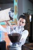 Primer del camarero que llena encima de la máquina de los granos de café Fotos de archivo libres de regalías