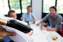 Primer del camarero que lleva una botella de vino Fotos de archivo
