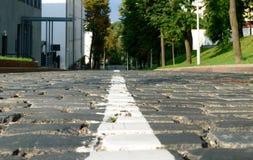 Primer del camino de la piedra de pavimentación Hierba verde y árboles en los lados Traff Foto de archivo libre de regalías