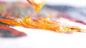 Primer del cepillo blanco grande que mancha la pintura de aceite anaranjado en la lona pintada acci?n Artes y conceptos de pintur metrajes