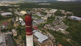 Primer del chimenea-tallo alto, rojo y blanco sobre los edificios de la zona industrial y de la f?brica rodeados por el bosque ve metrajes