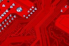 Primer del circuito electrónico rojo de la placa madre con el procesador Foto de archivo libre de regalías