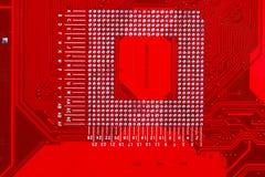 Primer del circuito electrónico rojo de la placa madre con el procesador Imagen de archivo libre de regalías