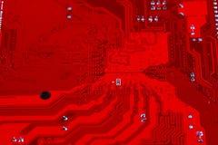 Primer del circuito electrónico rojo de la placa madre con el procesador Foto de archivo